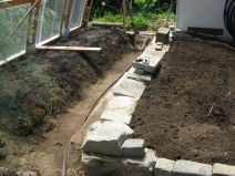 Garden raised bed construction. We reused granite curbs for a wall and thermal mass.